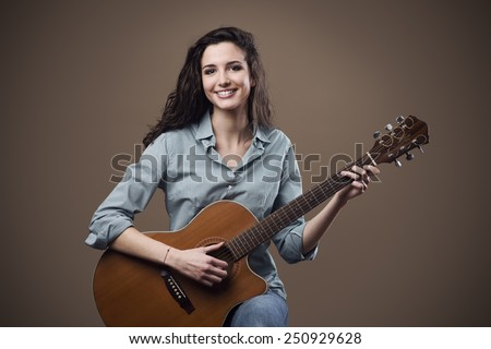 Beautiful young smiling girl playing acoustic guitar - stock photo