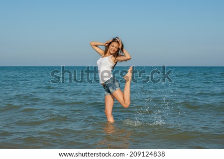 Beautiful young smiling girl splashing the water in the sea