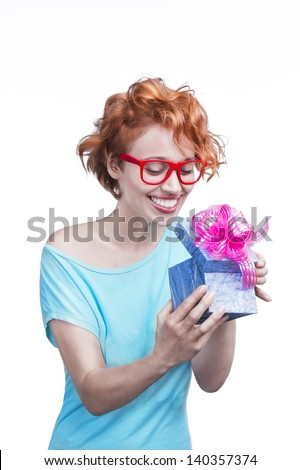 Beautiful young smiling girl with red hair holding a blue gift box with a bright pink bow on white background. Studio shot