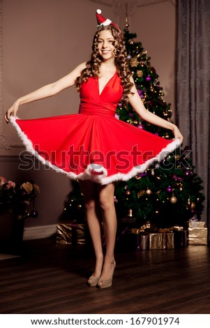Beautiful young smiling santa girl. Luxury wealthy woman in the Christmas interior. At the Christmas tree. - stock photo