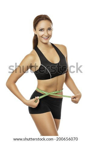 Beautiful young smiling sexy woman with athletic body in black sportswear measuring her waistline over white background. Health care, healthy nutrition, diet, slimming or weight loss results. - stock photo
