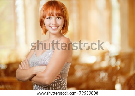 Beautiful young smiling woman has crossed hands on breast, against magnificent interior. - stock photo