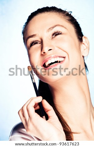 beautiful young smiling woman hold cosmetic brush, studio shot