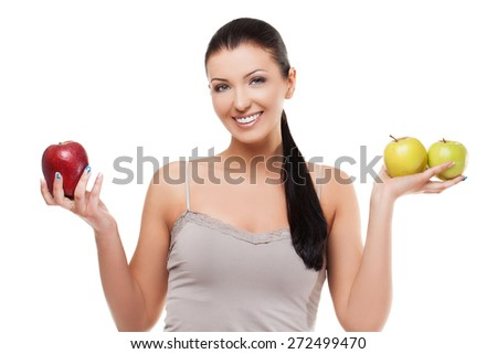 Beautiful young smiling woman holding two green apples and one red. Isolated over white background - stock photo
