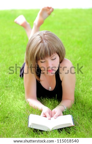 Beautiful young smiling woman laying on grass reading book, against green of summer park.