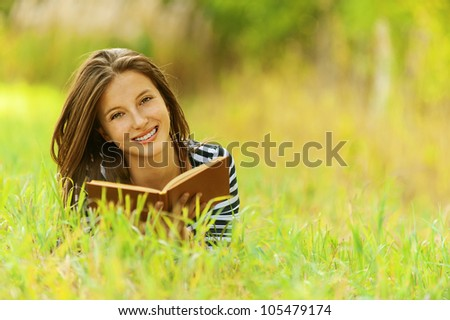 Beautiful young smiling woman lying on grass reading book, against green of summer park. - stock photo