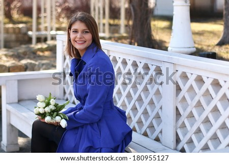Beautiful young smiling woman on a white wood bench in the park with fresh spring flowers
