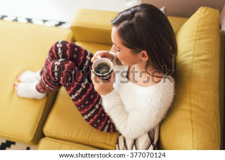Beautiful young smiling woman relaxing on sofa at living room while enjoying in coffee time. - stock photo
