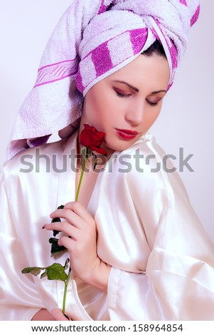 beautiful young smiling woman with a flower and towel on her head  - stock photo