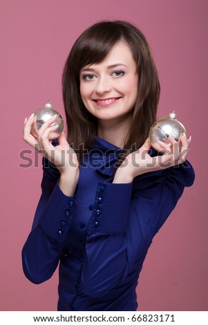 beautiful young smiling woman with Christmas decorations on a pink background