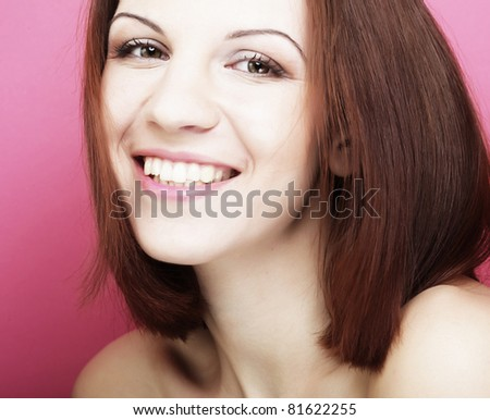 Beautiful young smiling woman with clean skin - over pink backgroud - stock photo