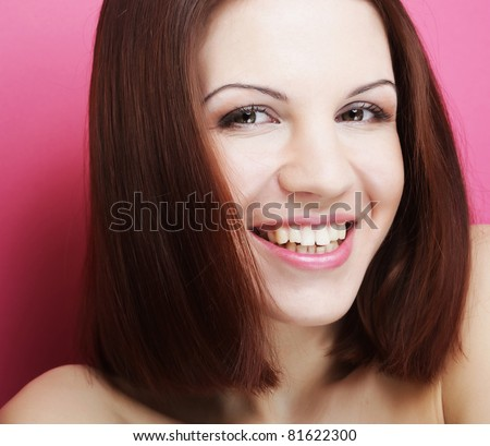 Beautiful young smiling woman with clean skin - over pink background - stock photo