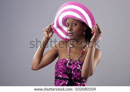 Beautiful young South African woman in bright colours striking a pose. - stock photo