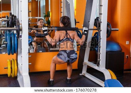 Beautiful young sports woman doing squats with a barbell in Smith Machine in the gym.