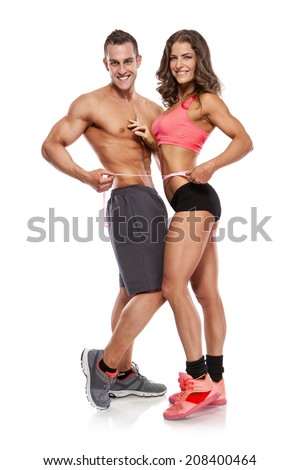 beautiful young sporty couple with a measuring tape isolated over white background