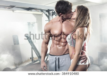 beautiful young sporty kissing  sexy couple showing muscle in gym - stock photo