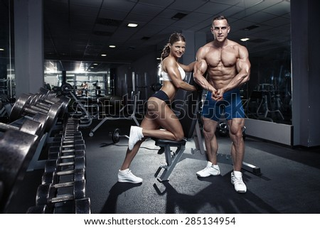 beautiful young sporty sexy couple showing muscle in gym - stock photo