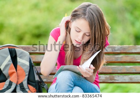 beautiful young student girl sitting on bench, holding exercise book in her hands and thinking. Summer or spring green park in background - stock photo