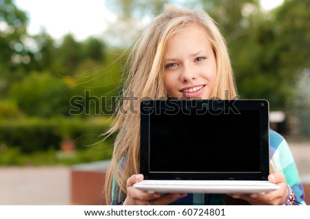 beautiful young student girl standing in park, smiling and looking into the camera, opened laptop with empty screen in her hands