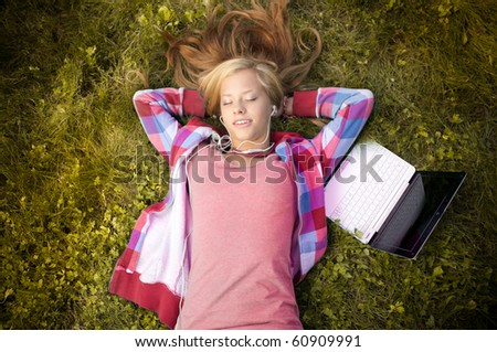 beautiful young student girl with laptop lying on grass in park, smiling with her eyes closed and listening to music - stock photo