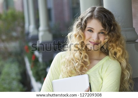 Beautiful young student holding a laptop outdoors - stock photo