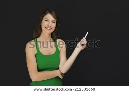 Beautiful young student over a black chalkboard with copyspace  - stock photo