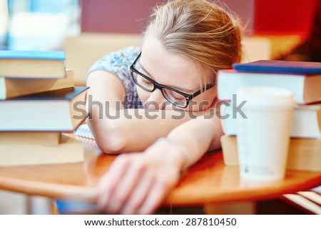 Beautiful young student with lots of books, sleeping on the table, tired of preparing for exams. Shallow DOF - stock photo