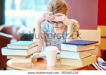 Beautiful young student with lots of books, studying or preparing for exams in a cafe. Shallow DOF - stock photo