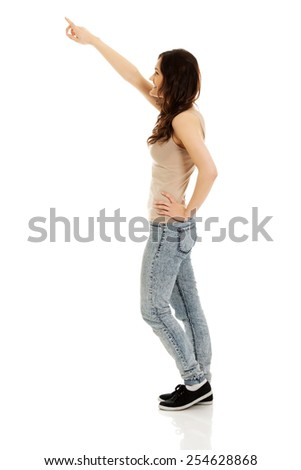 Beautiful young student woman pointing up - stock photo
