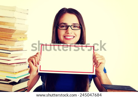 Beautiful young student woman wih stack of books and holding copy space. - stock photo