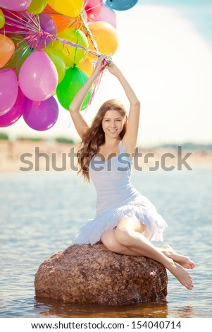 Beautiful young stylish woman with ainbow balloons in hands against the sky. Positive girl on nature. Smiling woman outdoors enjoying. - stock photo