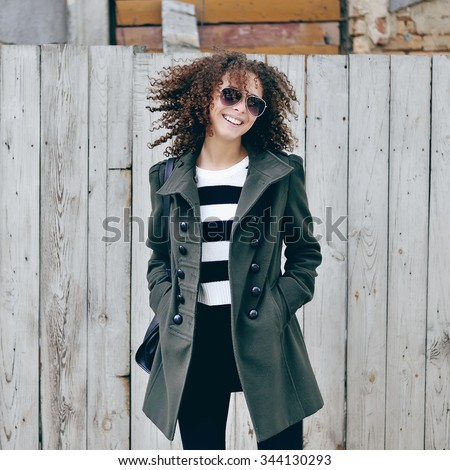 Beautiful young stylish woman with curly hair