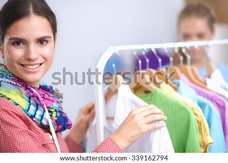 Beautiful young stylist near rack with hangers - stock photo