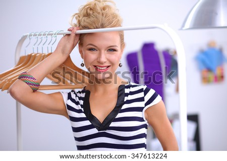 Beautiful young stylist near rack with hangers