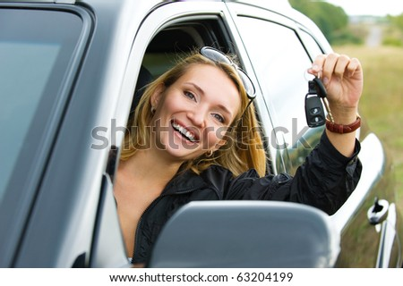 Beautiful young successful  woman in the new car with keys - outdoors - stock photo