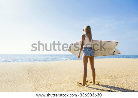 Beautiful young surfer girl checking the waves