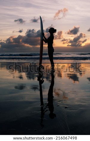 Beautiful young surfer girl in bikini with surfboard on a beach at sunset - stock photo