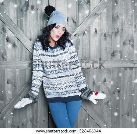 Beautiful  young surprised woman wearing winter hat and gloves covered with snow flakes. Christmas portrait concept.  - stock photo