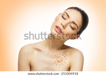 Beautiful young tanned girl with sun shape drawing on her chest - stock photo