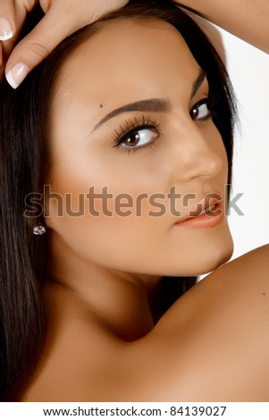Beautiful young tanned Italian woman with natural make-up and long hair smiling over her shoulder. - stock photo