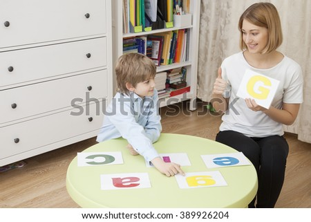 beautiful young teacher teaches letters with a cute Caucasian boy sitting at the green table. - stock photo