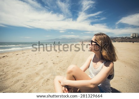 Beautiful young teen girl relaxing on Santa Monica beach in Los Angeles, California