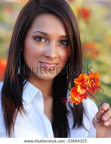 Beautiful young teenage girl holding a flower - stock photo