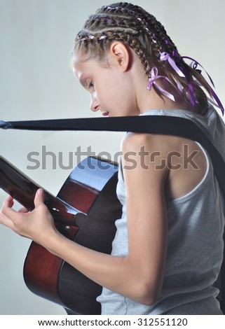 Beautiful young teenage girl playing acoustic guitar. Back view. - stock photo