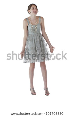 Beautiful young teenage girl with long brown hair dances in lacy silver party dress. Vertical, isolated on white with copy space.