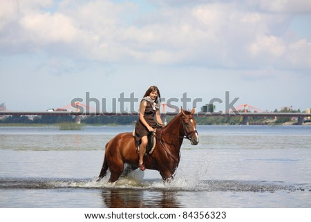 Beautiful young teenager girl in brown dress and chestnut horse riding in the water