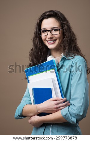Beautiful young teenager girl student posing with notebooks and smiling at camera - stock photo