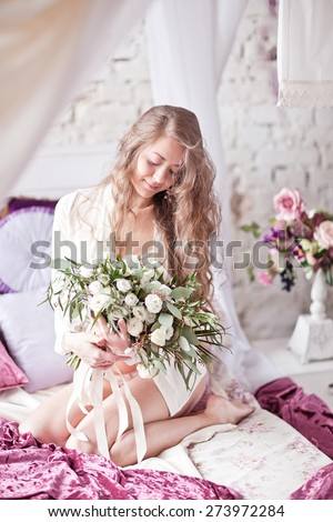 Beautiful young tenderness woman in night-shirt on the white vintage bed near pink pillow - stock photo
