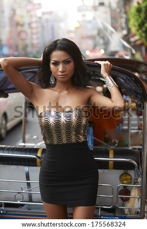 Beautiful young Thailand fashion model wearing elegant golden dress posting in busy Bangkok street on sunny day. - stock photo