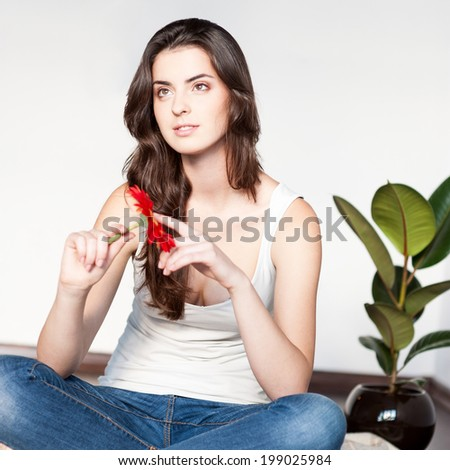 beautiful young thoughtful casual brunette woman sitting on wool plaid and holding red flower - stock photo